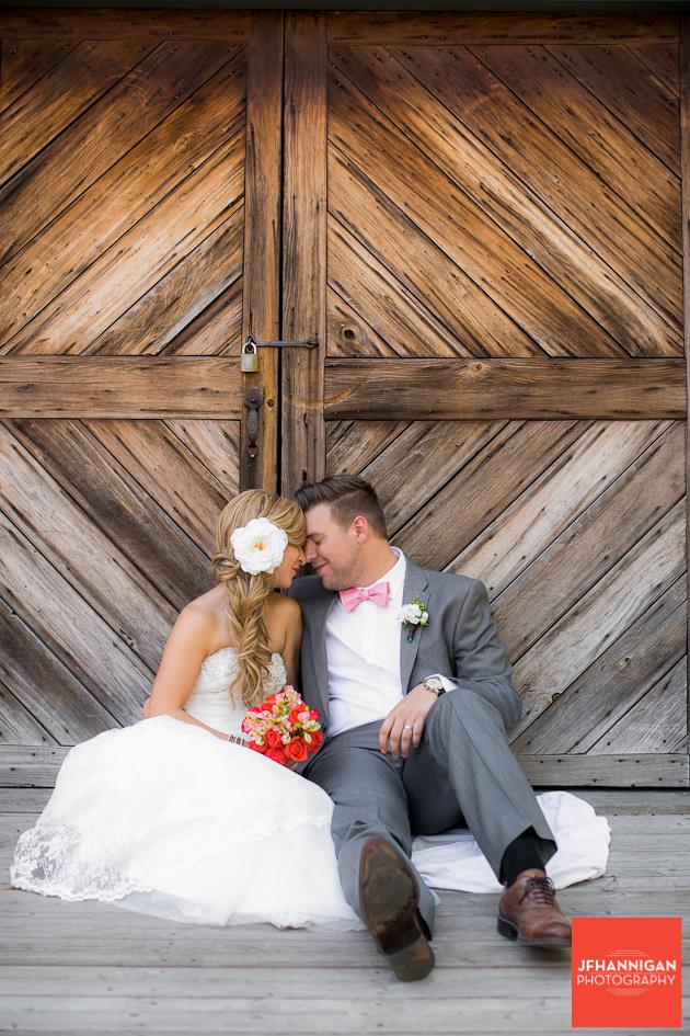 bride and groom sitting in front of barn doors Niagara Wedding Photographer