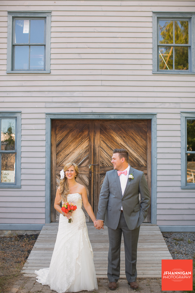 bride and groom standing in front of building at Wainfleet Heritage Village