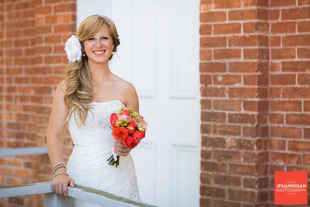 bride on porch of old brick building