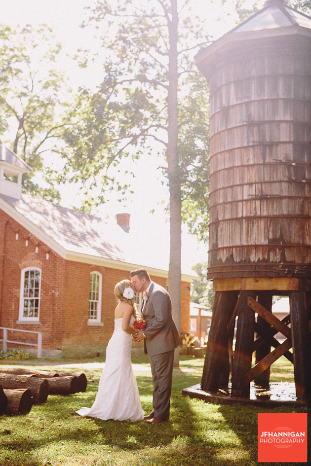 bride and groom kiss beside vintage silo
