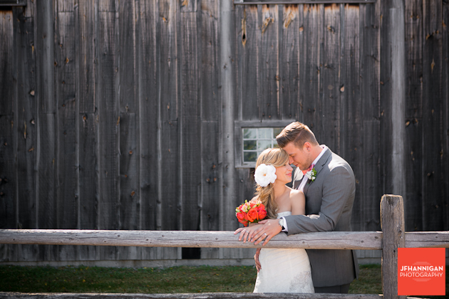 bride and groom by wood log fence in front of barn
