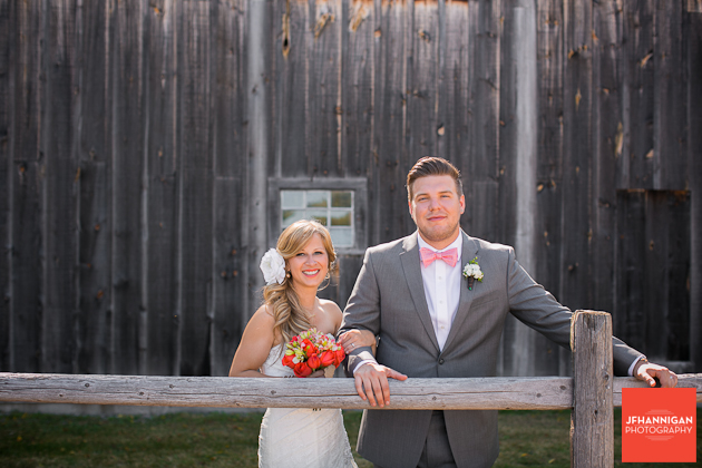 bride and groom posed at log fence in front of barn