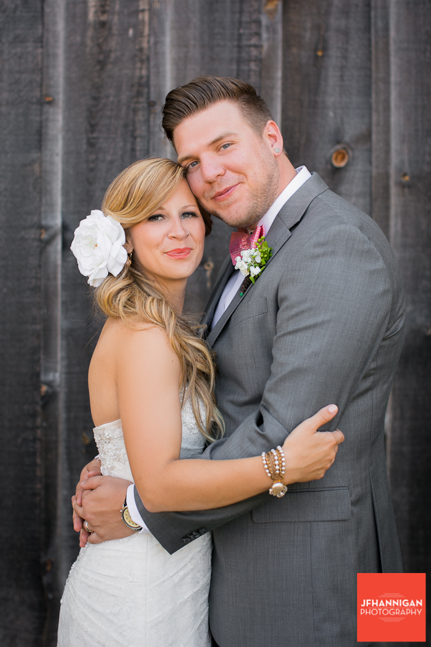 bride and groom portrait in front of barn