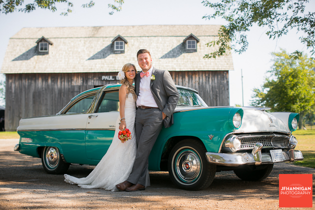 bride and groom by antique car and barn