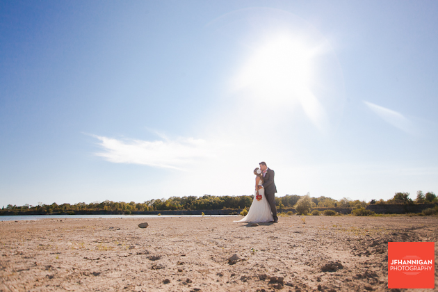 bride and groom kissing at water's edge