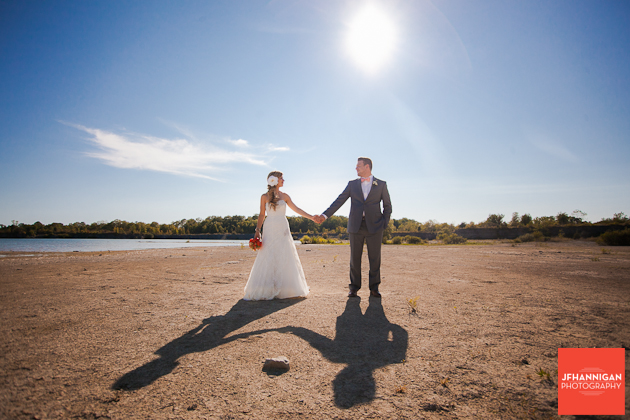 bride and groom holding hands by water's edge Niagara Wedding Photographer