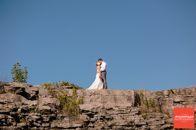 bride and groom kissing on rock cliff