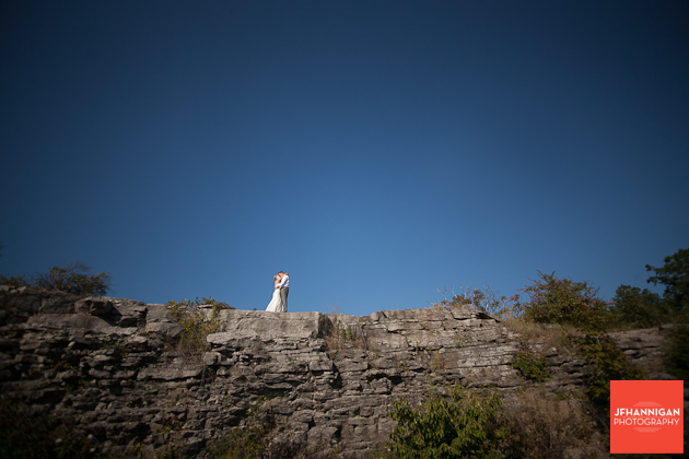 bride and groom standing on rock cliff