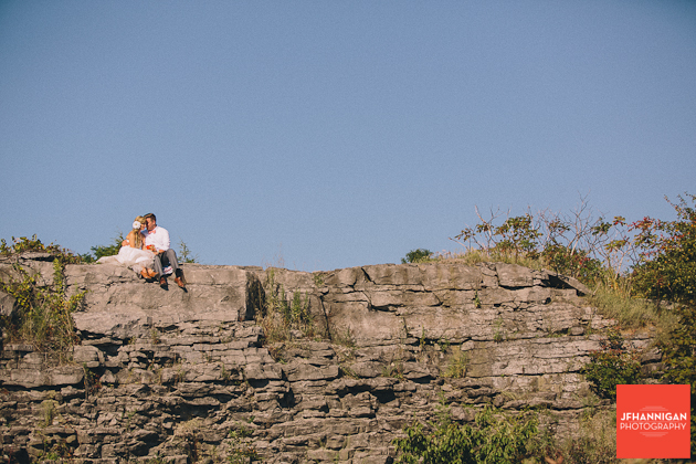 bride and groom sitting on rock cliff Niagara Wedding Photographer