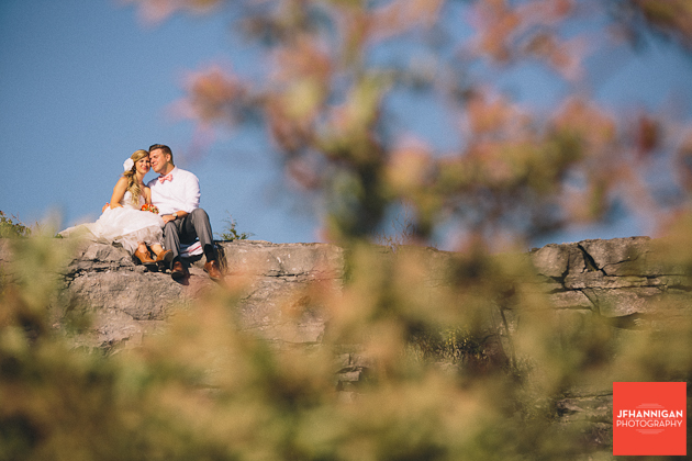 bride and groom sitting on rock cliff with folligae in foreground