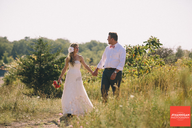 bride and groom walking in path among tall grass and small bushes