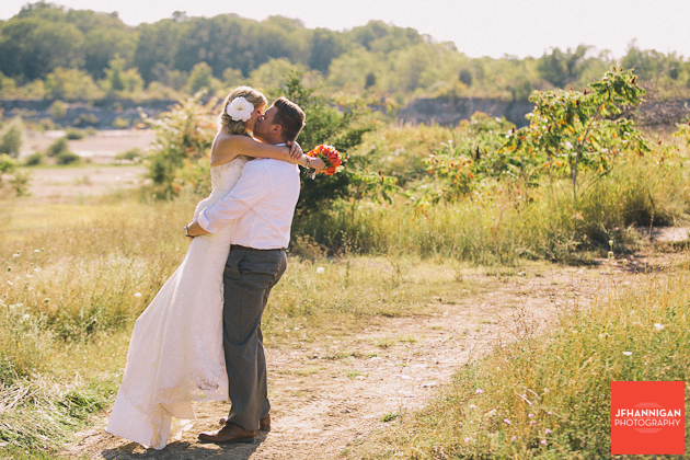 groom lifts bride off her feet for a kiss by quarry