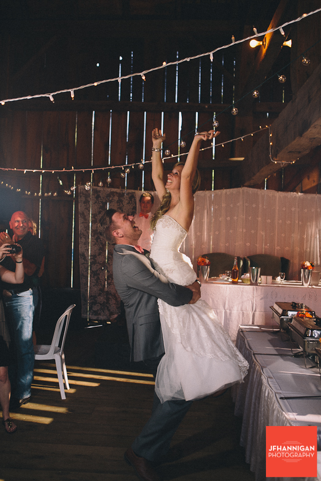 groom lifts elated bride in frong of buffet table at barn reception