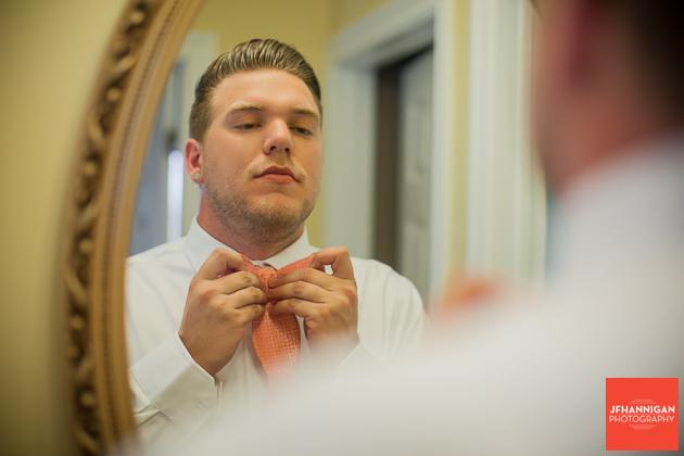 groom preparing bow tie in mirror