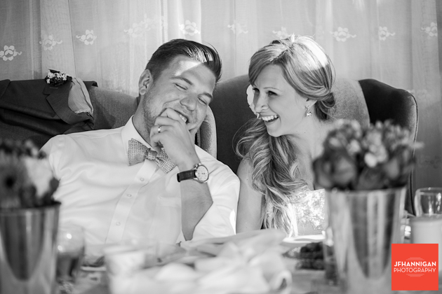 bride and groom laughing during receprtion speeches