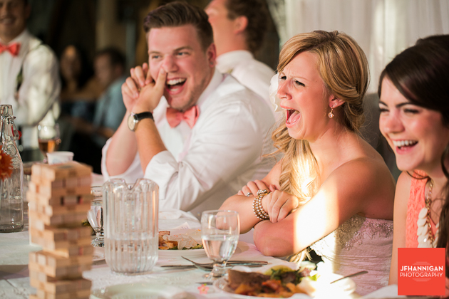 bride and groom laughing during speech at wedding reception