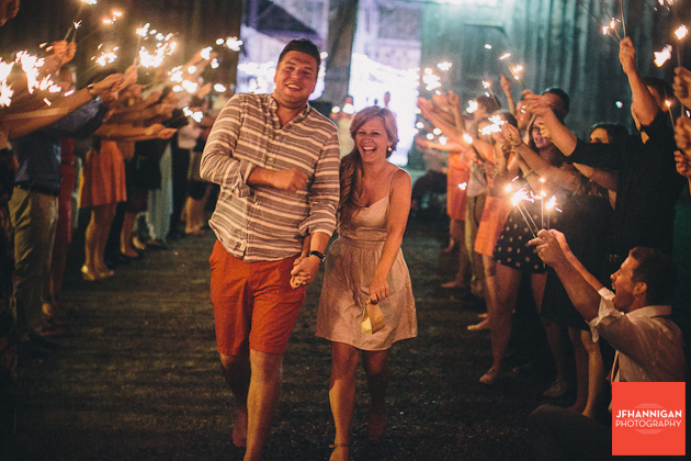 couple dressed in going away outfits greeted by reception guests and sparklers