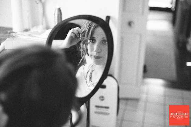 bride's attendant looking in mirror fixing hair