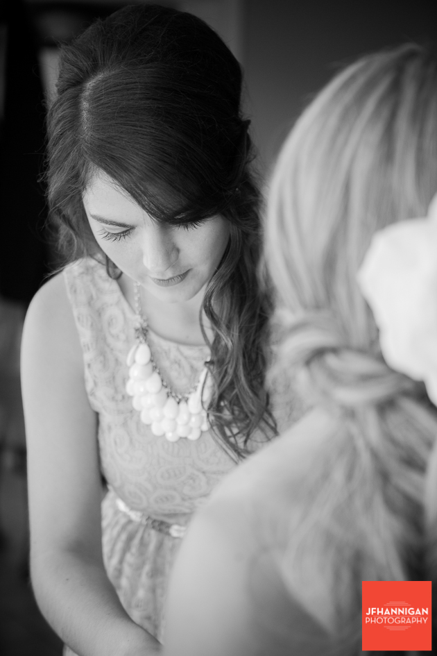 attendant lacing bride's wedding gown