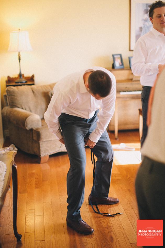 groomsmen putting on suspenders