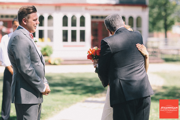 father hugging bride as groom watches